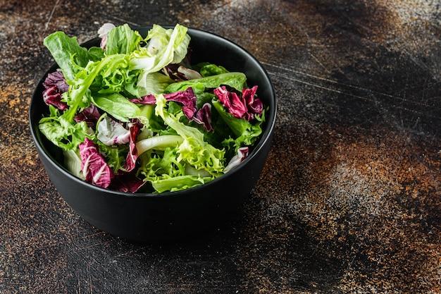 Bols avec des feuilles fraîches de laitue salade râpée mélangée, sur un vieux fond rustique sombre avec un espace de copie pour le texte