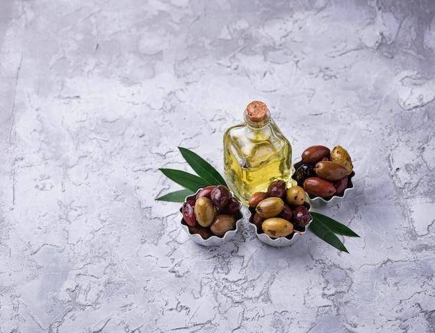 Bols avec mélange d'olives méditerranéennes marinées sur fond de béton. mise au point sélective