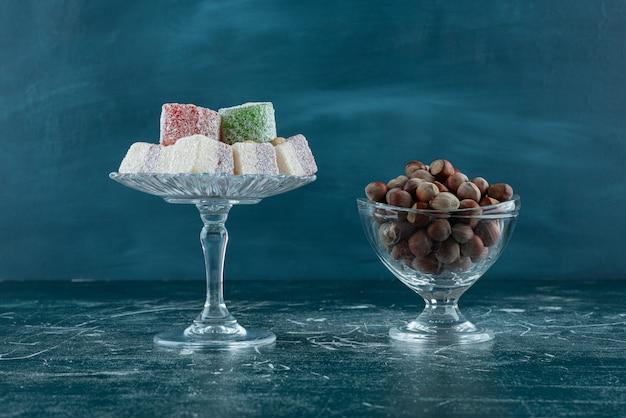 Bols de noisettes biologiques et délices sucrés sur une surface en marbre.