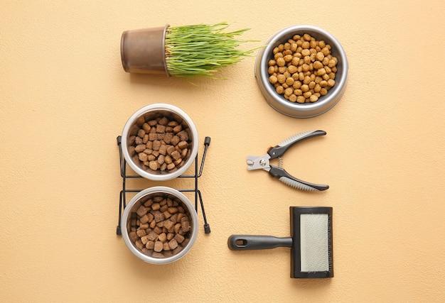 Bols avec nourriture pour animaux et accessoires sur fond de couleur