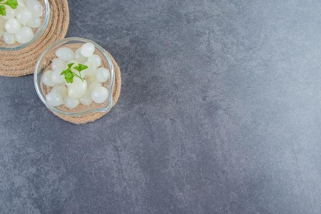 Bols d'oignon mariné sur dessous de plat, sur le fond de marbre.