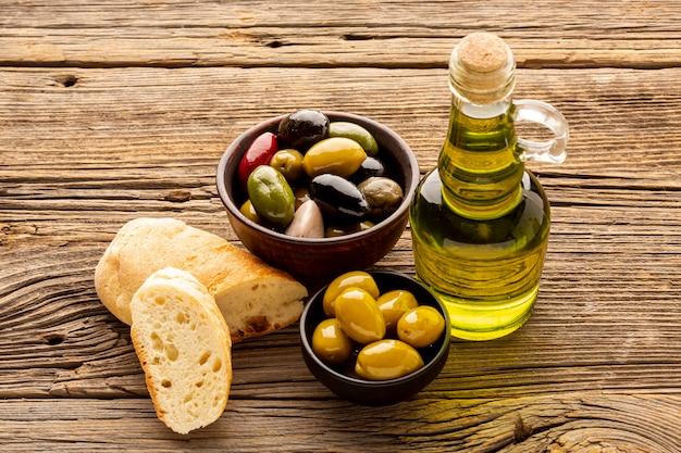 Bols d'olives à angle élevé, tranches de pain et bouteilles d'huile