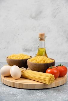 Bols de pâtes crues, œufs, tomates et huile d'olive sur une surface en marbre.
