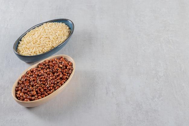 Bols pleins de haricots crus et de riz long sur table en pierre.