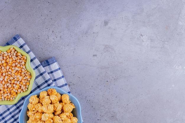 Bols pleins de maïs soufflé et de maïs soufflé enrobés de caramel sur une serviette sur fond de marbre. photo de haute qualité