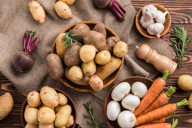 Bols avec pommes de terre carotte et ail sur table