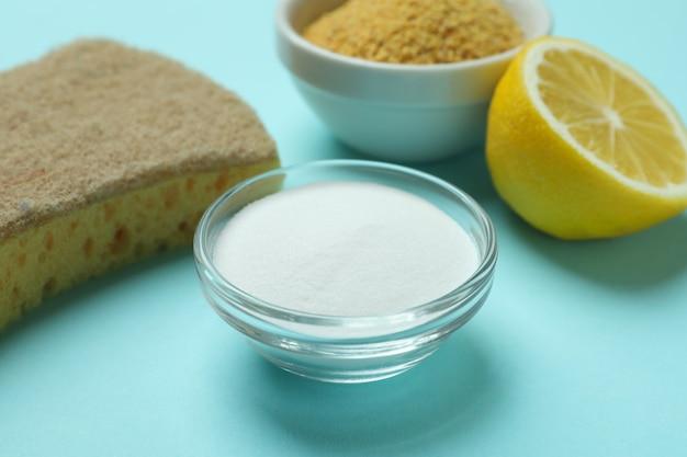 Bols avec poudre de moutarde et poudre acide, éponge et moitié de citron sur fond bleu isolé
