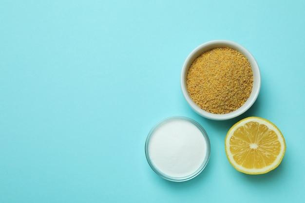 Bols avec poudre de moutarde et poudre d'acide, et la moitié de citron sur fond bleu isolé