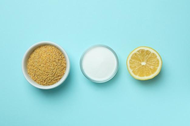 Bols avec poudre de moutarde et poudre d'acide, et la moitié de citron sur fond bleu