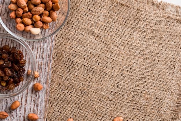 Bols avec des raisins secs, des arachides et sur une table en bois. vue de dessus. espace de copie. place pour votre inscription