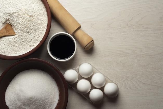 Des bols remplis de farine, de sucre et de sauce, des œufs et un rouleau à pâtisserie