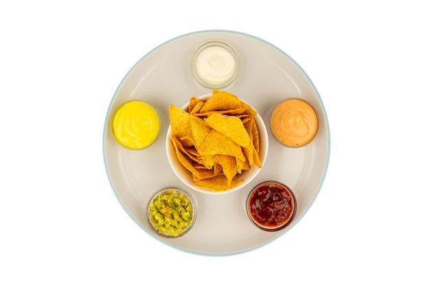 Bols à sauce mexicaine sur une assiette en céramique avec des chips tortilla au centre.