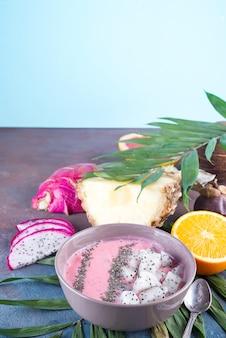 Bols de smoothie rouge ou rose aux framboises garnies de graines de pitaya et de chia fraîches sur une feuille de palmier sur fond de pierre, espace copie