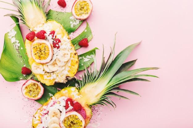 Bols à smoothies servis à l'ananas coupé sur rose
