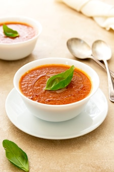 Bols de soupe froide de tomate gaspacho au basilic et deux cuillères sur fond clair