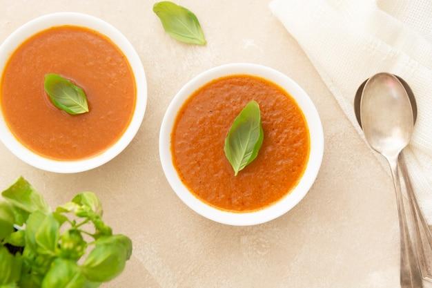 Bols de soupe de tomate froide au gaspacho avec basilic et deux cuillères sur fond clair vue de dessus