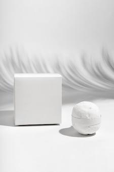 Bombe de bain blanche vue de face à côté de la boîte