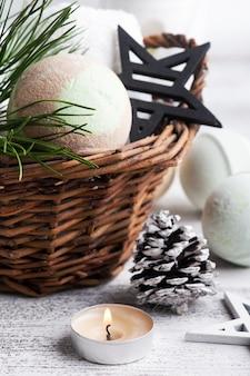 Bombe de bain dans le panier en composition spa de noël avec des branches de pin et des étoiles, bougie allumée