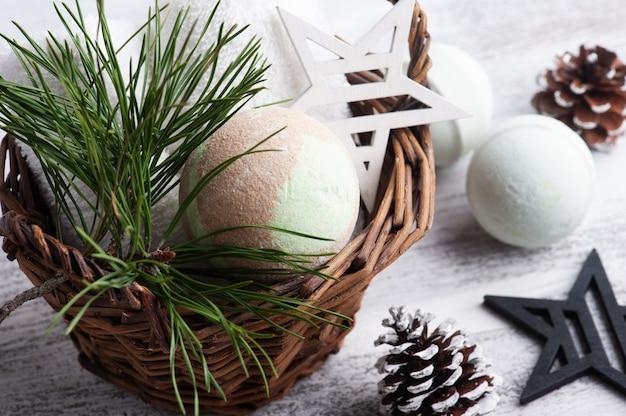 Bombe de bain dans le panier en composition de spa de noël avec des branches de pin et des étoiles