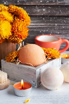 Bombes de bain aromatiques en composition spa avec fleurs orange et serviettes. arrangement d'aromathérapie, nature morte zen avec des bougies allumées