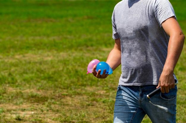 Des bombes à eau colorées en été prêtes à jouer. tenir des ballons à la main.