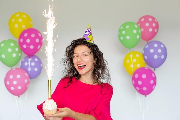 Bon anniversaire. fille brune sexy posant avec des ballons, des feux d'artifice, des ballons colorés et un gâteau de vacances sur fond blanc.
