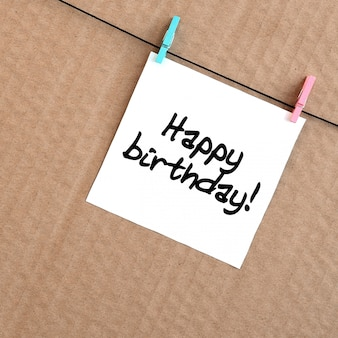 Bon anniversaire! la note est écrite sur un autocollant blanc qui pend avec une pince à linge sur une corde sur un fond de carton brun