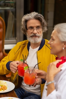 Bon auditeur. homme barbu assis à côté de sa femme dans le café de la rue avec un verre à la main et écoutant un discours de sa femme.