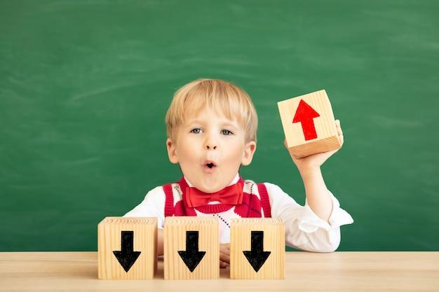 Bon choix! étudiant enfant surpris en classe contre tableau vert.