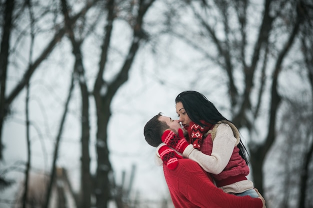 Bon couple embrassant dans les bois d'hiver