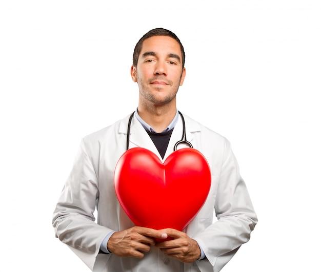 Bon docteur tenant un coeur de jouet sur fond blanc