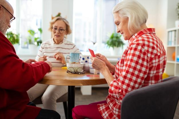 Bon jeu. belle femme âgée tenant ses cartes à jouer tout en jouant avec ses amis