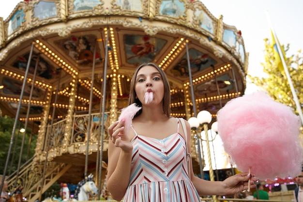 Bon à la jolie jeune femme aux cheveux bruns en robe romantique debout sur carrousel dans le parc d'attractions, manger de la barbe à papa sur bâton en bois