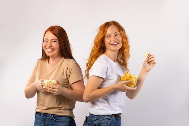 Bon moment à passer. les filles aux cheveux roux mangent des chips et popcrn, rient et se détendent. photo sur mur blanc. q