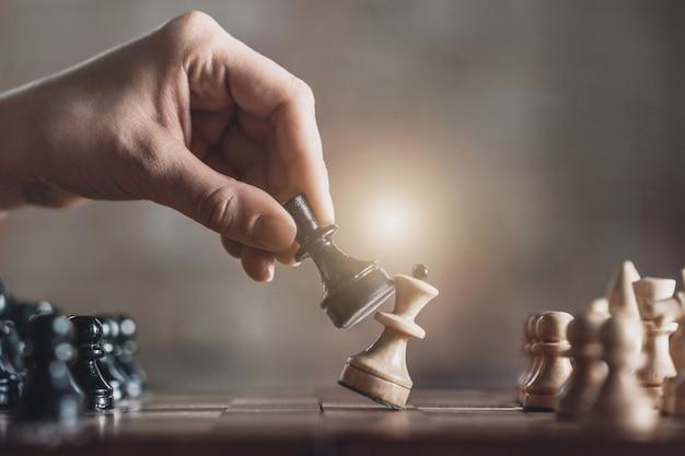 Bon mouvement. la main des joueurs tenant le pion noir battant la reine blanche sur l'échiquier n'est pas visible