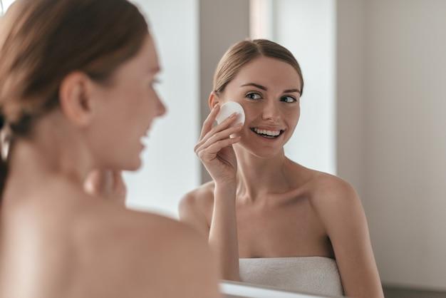 Bon soin de sa peau. sur l'épaule d'une jeune femme nettoyant sa peau avec un coton tout en se regardant dans le miroir