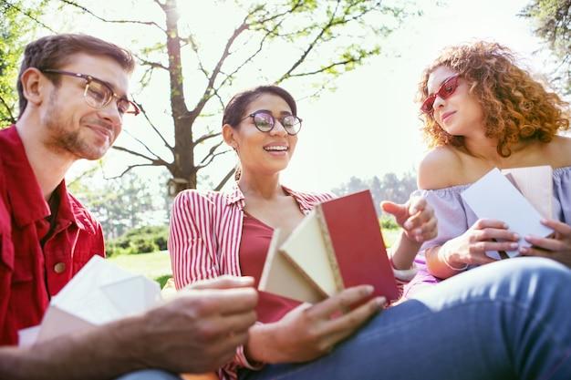 Bon travail. contenu femme brune assise en plein air avec ses collègues et discutant de leur démarrage