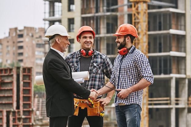 Bon travail ingénieur âgé gai en tenue de soirée et casque blanc tenant des dessins techniques et