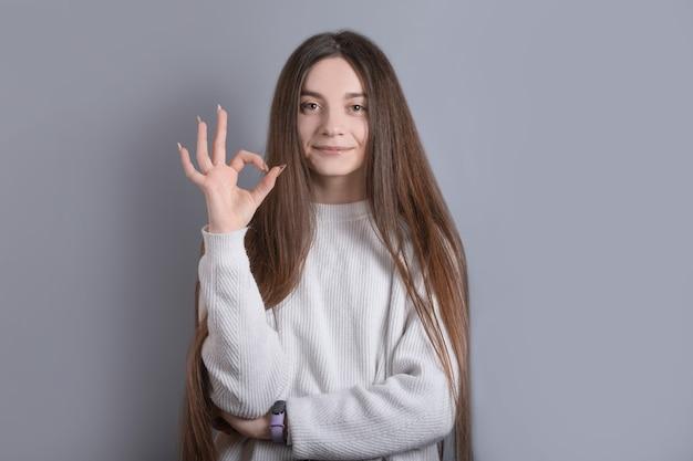 Bon travail. portrait de jolie fille caucasienne élégante moderne et insouciante de longs cheveux châtains montrent bien