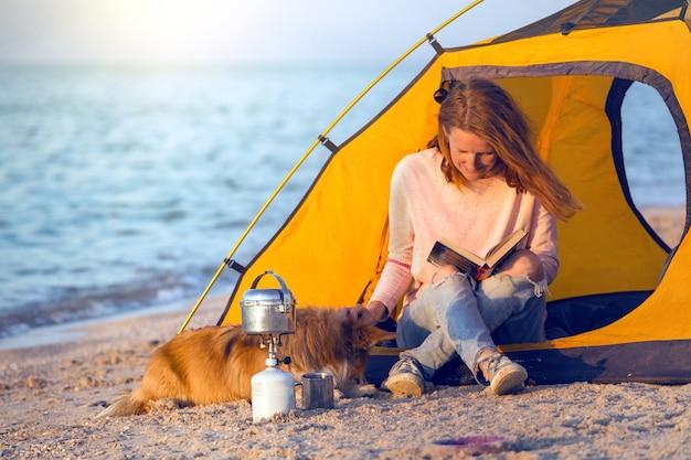 Bon week-end au bord de la mer - fille avec un chien dans une tente sur la plage à l'aube. paysage ukrainien à la mer d'azov, ukraine