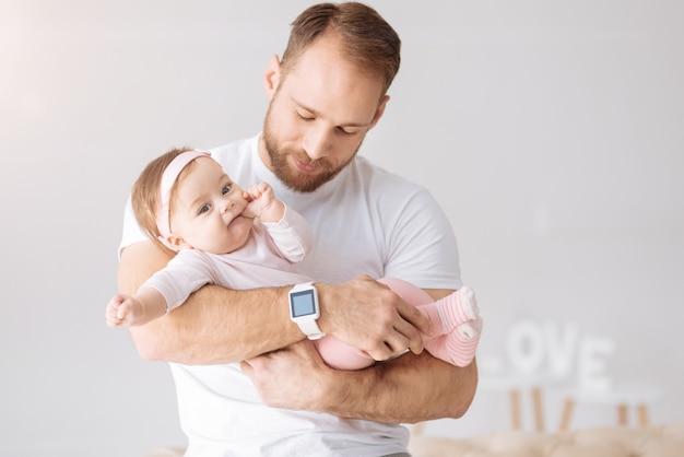 Bon weekend. charmante jolie petite fille couchée dans les mains du père et regardant ailleurs tout en exprimant son intérêt et sa joie