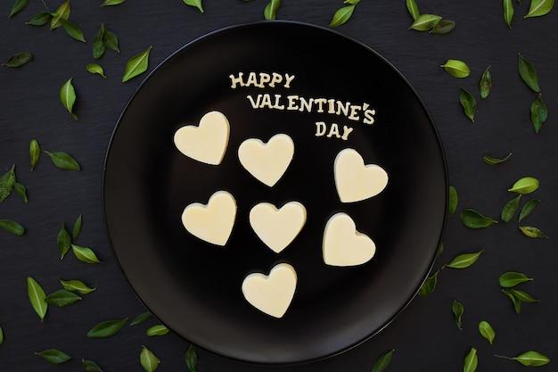 Bonbon blanc chocolat inscription en forme de coeur happy valentine sur une plaque noire avec des feuilles vertes