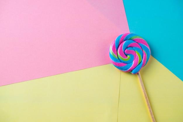 Bonbon sucette lumineuse sur fond coloré, coup plat
