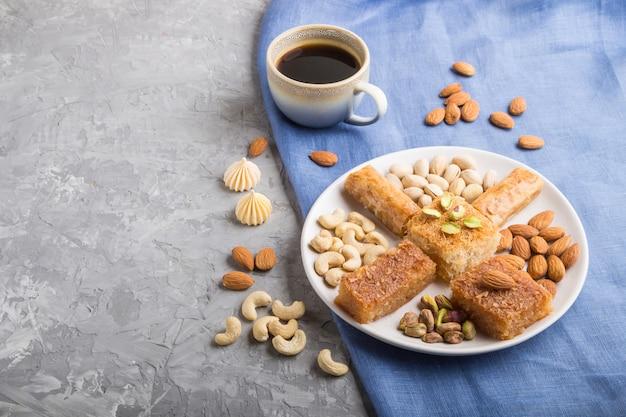 Bonbons arabes traditionnels (basbus, kunafa, baklava), une tasse de café et des noix sur une surface latérale en béton gris, copie espace.