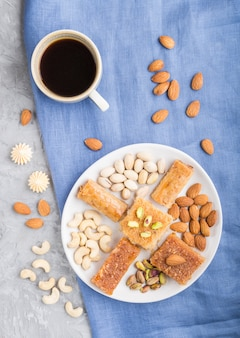 Bonbons arabes traditionnels (basbus, kunafa, baklava), une tasse de café et de noix sur une surface supérieure en béton gris, vue de près.