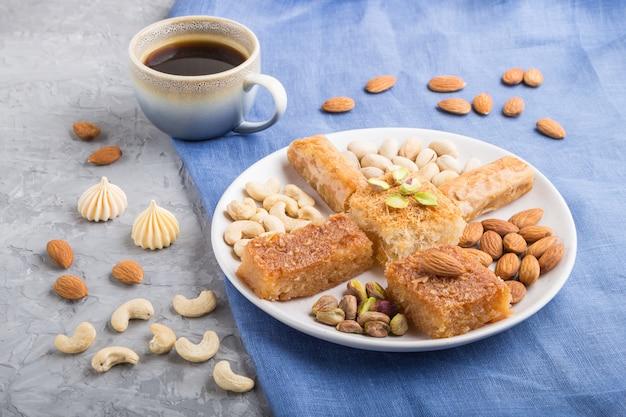 Bonbons arabes traditionnels (basbus, kunafa, baklava), une tasse de café et noix vue de côté, gros plan.