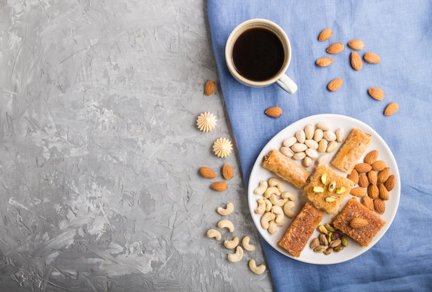 Bonbons arabes traditionnels (basbus, kunafa, baklava), une tasse de café et noix vue de dessus