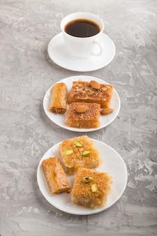 Bonbons arabes traditionnels sur plaque blanche et une tasse de café. vue de côté.