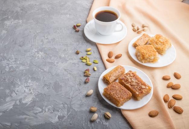 Bonbons arabes traditionnels et une tasse de café sur un fond de béton gris. vue latérale, espace copie.