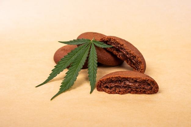 Bonbons au cannabis, biscuits aux pépites de chocolat avec plante de marijuana à feuilles vertes.